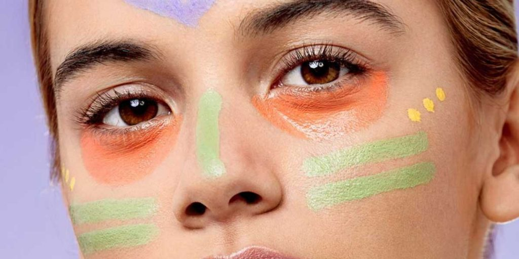 Woman with color correctors on face